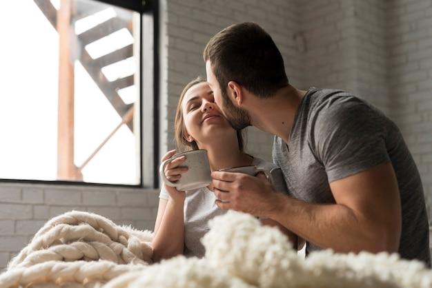 ベッドでコーヒーを飲んでロマンチックな若いカップル
