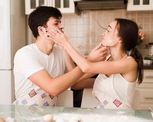 愛らしい若い男性と女性の食べ物で遊ぶ