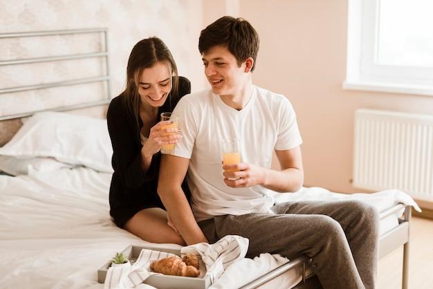 ベッドで朝食を持っているロマンチックな若いカップル