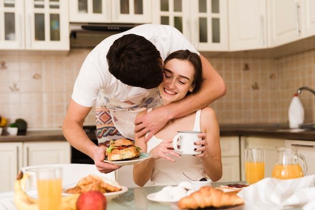 Прелестный молодой человек, подающий завтрак с подругой
