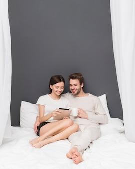 Счастливая пара смотрит на планшет