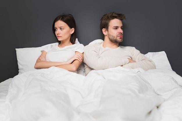 ベッドで怒っている朝のカップル