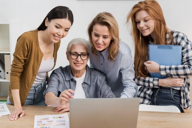 Группа женщин, работающих вместе на ноутбуке