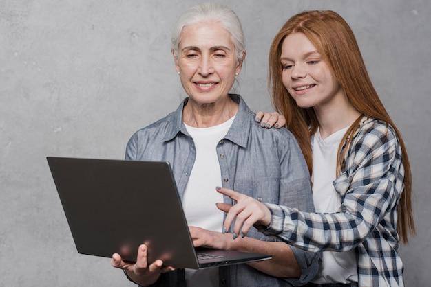 Красивая молодая и зрелая женщина, глядя на ноутбук