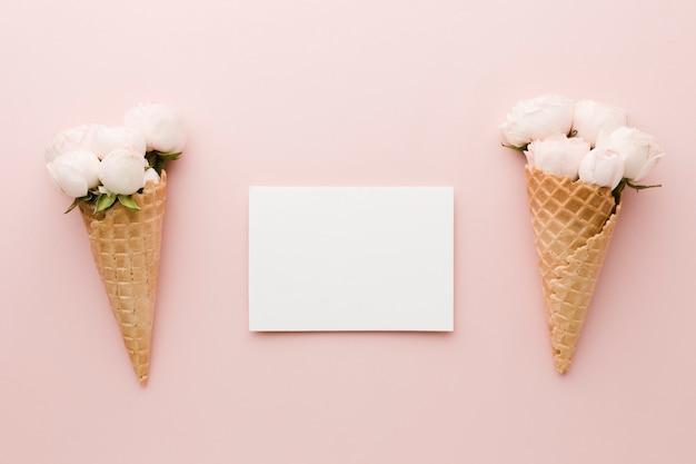 空のカードと花のアイスクリームコーンのトップビュー