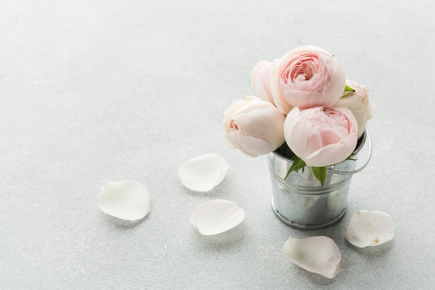 金属製のバケツと花びらのバラ