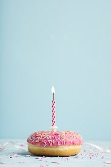 点灯ろうそくとコピースペースで誕生日ドーナツの正面図