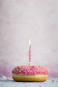 Вид спереди глазированного пончика с зажженной свечой и копией пространства