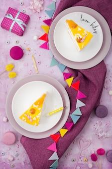 Вид сверху кусочков торта на тарелках с подарком и гирляндой