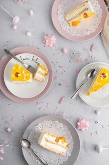 Вид сверху кусочки торта на тарелках со столовыми приборами