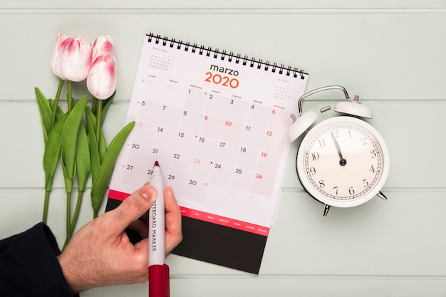 時計とカレンダーの横にあるチューリップの花束
