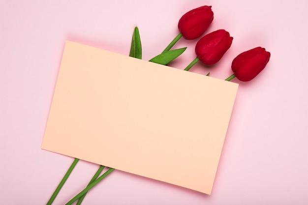 グリーティングカードと赤いチューリップの花束