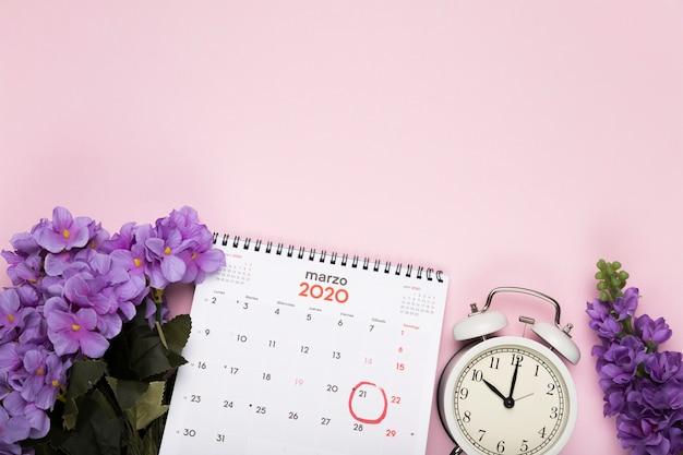 カレンダーと時計の横にある花の花