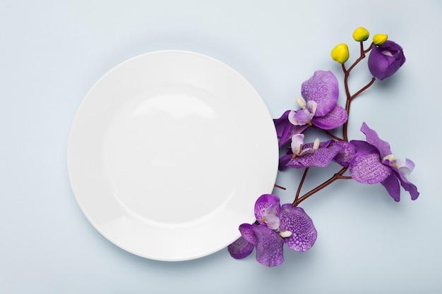Цветущие цветы с белой тарелкой
