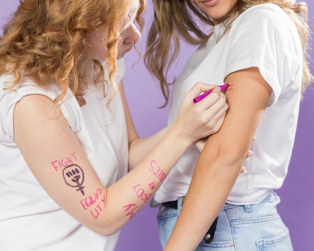 抗議のための友人の腕を塗るクローズアップ女性