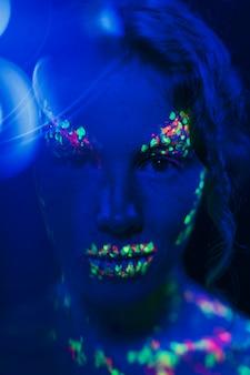 カラフルな蛍光メイクを持つ女性のクローズアップビュー