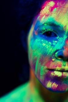 蛍光化粧を持つ女性のクローズアップビュー