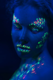 クローズアップ目と紫外線塗料を持つ女性