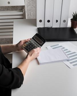 Высокий угол бизнес женщина, держащая калькулятор