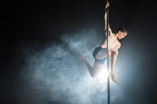 ポールダンスを実行する強力な男性モデルの肖像画