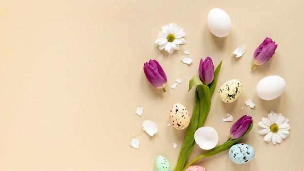 Вид сверху цветы и крашеные яйца на столе