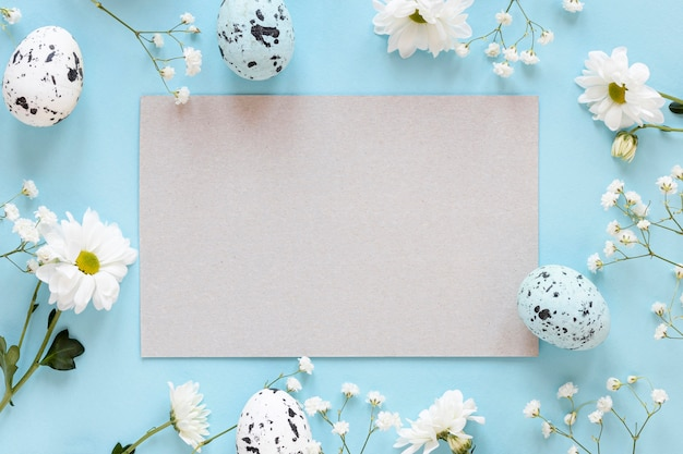 Рамка из цветов с листом бумаги и яйцами