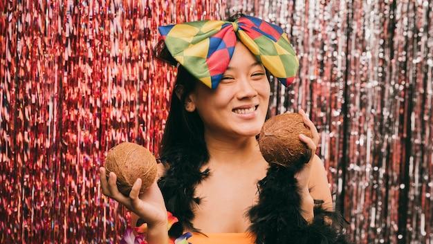 ココナッツとカーニバルパーティーでスマイリー女性