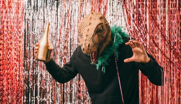 恐竜の衣装でシャンパンのボトルを持つ男性