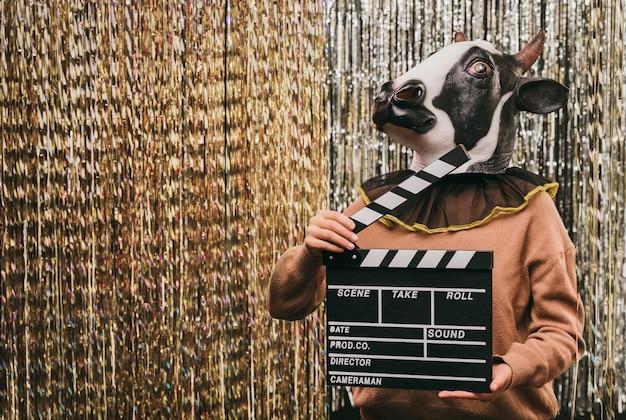 映画のスレートと牛の衣装の女性