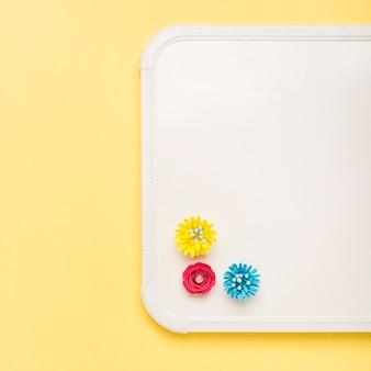 ホワイトボードにカラフルな紙の花のトップビュー