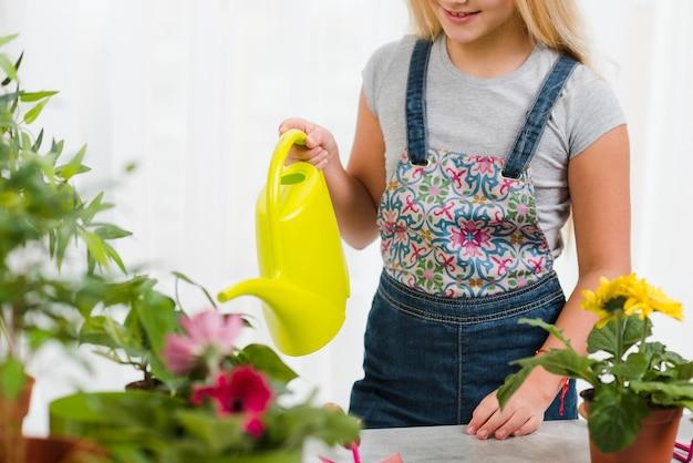 Крупным планом молодая девушка поливает цветы