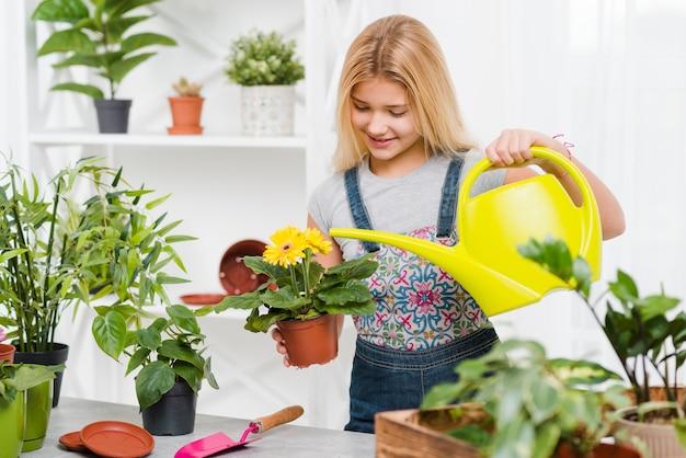Улыбающаяся девушка поливает цветы