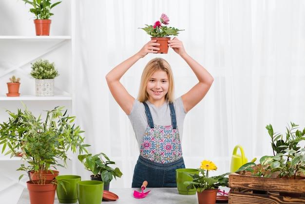 Молодая девушка держит горшок с цветами
