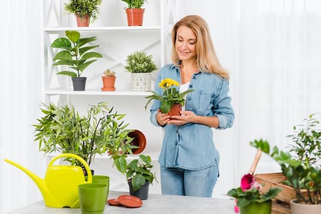 Высокий угол женщина, держащая цветочный горшок