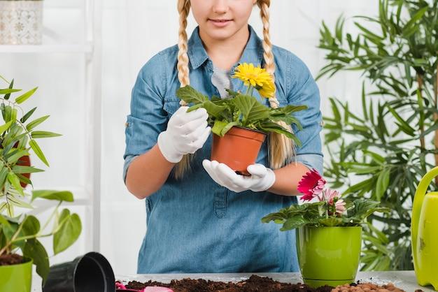 Маленькая девочка конца-вверх держа цветочный горшок