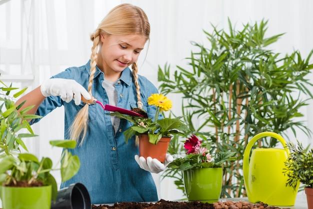 Молодая девушка ухаживает за цветами в теплице