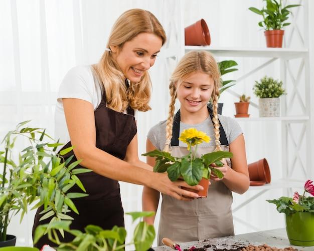 高角度の娘と母が花を植える