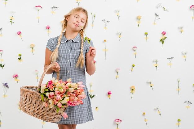 花を持つバスケットを保持している若い女の子