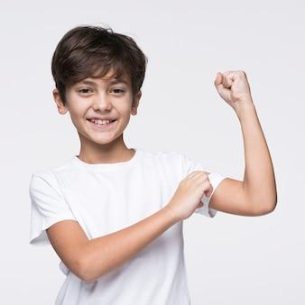 彼の筋肉を示す少年