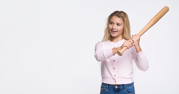 若い女の子が野球のバットで打つ準備