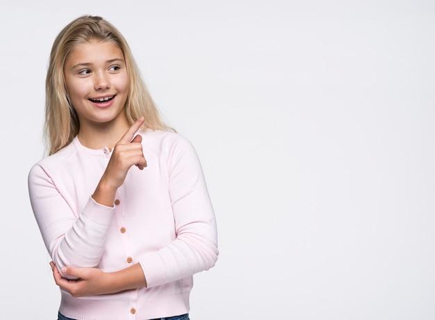 Смайлик молодая девушка, указывая с копией пространства