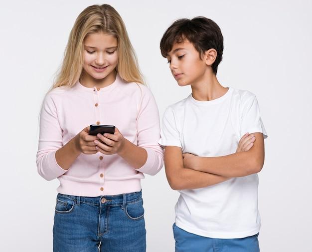 Маленький брат смотрит на телефон сестры