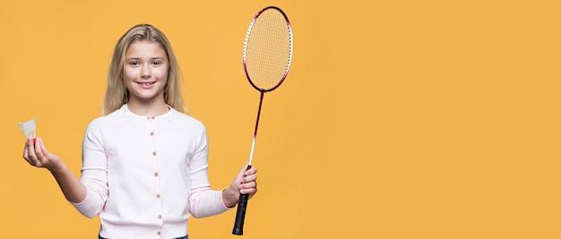 Молодая девушка играет в теннис с копией пространства