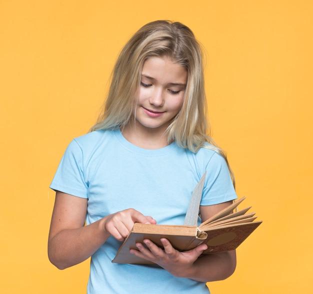黄色の背景で読んでいる若い女の子