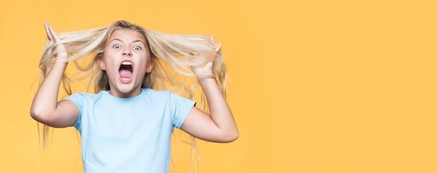 Игривая молодая девушка с желтым фоном