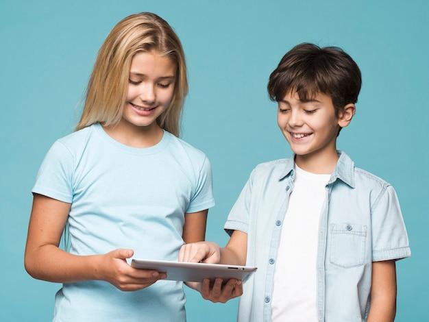 Молодые братья и сестры вместе с помощью планшета