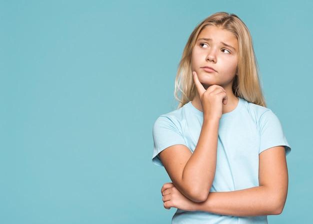 Молодая девушка думает с копией пространства