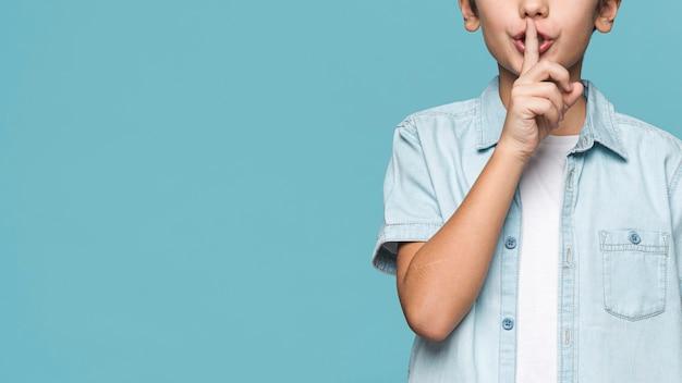 沈黙のサインを示すクローズアップ少年