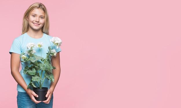 フラワーポットを保持している若い女の子