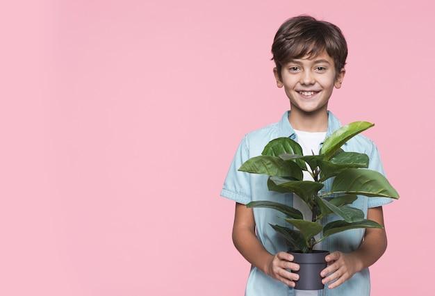 Улыбающийся мальчик держит цветочный горшок